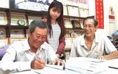 劉為安先生(左一)正在簽名贈書給文友。