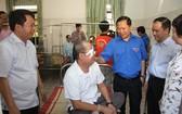 越南中央青聯會主席阮飛隆(藍衣)對動手術後的病人表示慰問。(圖源:共青團中央官方網站)