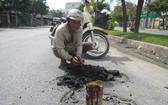 梅文福先生正在修補路面。