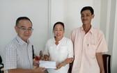圖1:本報編委兼編輯部主任范興亦把建屋經費轉交予第八郡紅十字輔助會會計阮氏理。