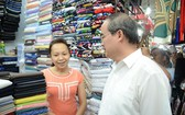 市委書記阮善仁看望安東市場,並詢問了某一布販的生意情況。(圖源:ĐL)