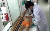 醫生正在給得瘧疾病兒治療。