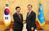 政府副總理、外長范平明(左)與韓國總統文在寅握手合影。(圖源:韓聯社)
