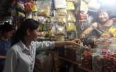 平西市場華人商販向顧客介紹蜜餞。