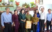 國家副主席鄧氏玉盛(左三)探望並向榮軍家庭阮楊永贈送禮物。