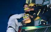 消防員搶救一名兒童離開火警現場。