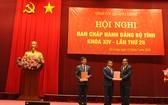 中央組織部常務副部長阮清平向黎光松、阮文勝兩位同志頒發黨中央政治局的幹部輪換部署《決定》。