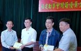 市民族處副主任梁鴻德(左一)與溫陵會館 理事長張子諒(右一)頒發獎學金給碩士畢業生。