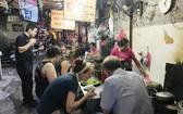 導遊向外國遊客介紹河內市同春街市小食。