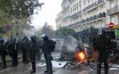 防暴警察在巴黎市中心正在燃燒的車輛前嚴密警戒。(圖源:互聯網)