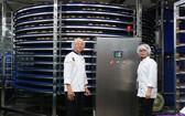 亞洲餅家總經理高肇力(左)視察全自動設備的生產情況。