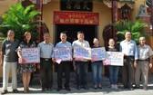 浸石天后宮副理事長張興盛(右二)與諸 位理事代表向各受惠單位轉交春節濟貧善款。