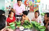 同奈省天平孤兒 院小朋友們正品嚐志願者所烹煮的飯菜。