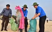 穿綠色志願青年制服和戴漁夫帽的潘玉壽同志(中)步入順安海灘打掃,清理垃圾。(圖源:明晰)