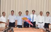 新任第二郡人委會副主席阮白黃鳳(中)接過人事委任《決定》和鮮花祝賀後與市領導合照。(圖源:Đ.Quân)