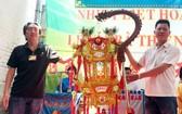 群賓會館值理會副主席陳志豪(左) 把第六盞聖燈交給鄭家福先生。