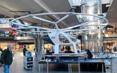 """5月12日,德國Volocopter公司在柏林火車總站內展示其推出的""""空中計程車""""原型機,吸引過往乘客駐足端詳。(圖源:互聯網)"""