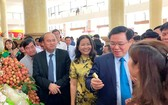 政府副總理王廷惠(前右二)在經濟論壇場外參觀北江省推介的各種農產品。(圖源:誠鐘)