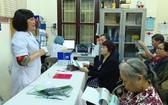 醫生給河內市二徵女王郡參加者講解大直腸癌及早篩查資訊。(圖源:M.T)