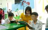 安平銀行副總經理阮氏香與小學生閱讀由該項目贈送的書本。