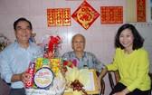 第十一郡人委會主席陳氏碧蓮(右)和郡高齡人會主席朱杞文(左)向華人長者蕭德鈞大叔贈送禮物。