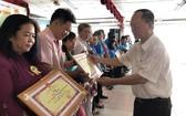 穗城會館理事長盧耀南向越華模範家庭頒發獎狀。
