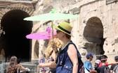 6月28日,在意大利羅馬鬥獸場,人們撐傘遊覽躲避烈日。(圖源:新華社)