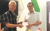 徐有燦(左)報效本報社會慈善金予本報代表接領。