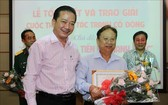 市文體廳副廳長武仲南(前左)向金甌省參賽者黎越鴻頒發一等獎并送鮮花祝賀。(圖源:越通社)