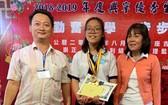 崇正興寧福利組理事長鄒國榮(左一) 向模範生鍾貴彩頒發獎學金。