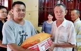 沙瀝市明月居士林林長江忠盛(右)向窮人發禮品。