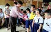 鄧氏宗祠理事長鄧栢榮向小學生們頒獎。