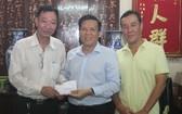 本報主編阮玉英(右二)接受周華邦住持贊助善款。