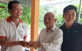 李庭輝總務(中)向安江省安富縣永厚鄉紅十字會移交建溫情屋經費。
