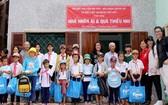 西貢作家分會成員們與清貧好學生、阮玉英在仁愛屋前合影。