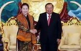 國會主席阮氏金銀與老撾總書記、國家主席本揚握手。(圖源:越通社)