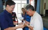 郡越南祖國陣線委員會主席黎晉才贈送 禮物給長者。