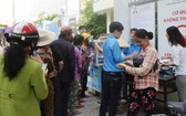 窮人排隊等待領取慈善百貨攤位的免費生活用品。