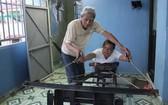 陳煌明研究製造出讓孩子們鍛煉手力的一台機。圖片中是陳煌明與韋氏姮。