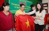 市越南祖國陣線委員會副主席趙麗慶(右一)將國旗贈予芹耶縣漁民。(圖源:勞動者報)