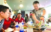 源味火鍋店老闆董先生親自為食客服務。