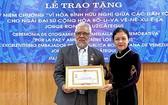 阮芳娥大使(右)代表VUFO領導向委內瑞拉共和國特命全權大使豪爾赫‧隆東‧烏斯卡特吉頒贈紀念章。(圖源:越通社)