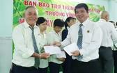 董事長陳金泉(右)頒發獎金給老師、員工。
