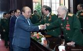 政府總理阮春福(前左)與退伍軍人交談。(圖源:Chinhphu.vn)