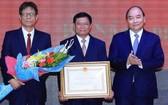政府總理阮春福(右)向第三區域政治學院頒授一等勞動勳章。(圖源:越通社)