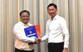 新任第十一郡人委會主席陳飛隆(左)從市人委會副主席陳永線手中接過人事委任《決定》。(圖源:VOH)