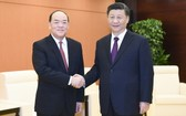 中國國家主席習近平(右)會見賀一誠。(圖源:新華社)