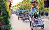 國際遊客坐三輪車參觀會安古埠。