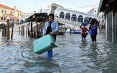 當地時間12月23日,意大利威尼斯的里亞托橋附近,一名女性拎著箱子涉水而行。 (圖源:路透社)