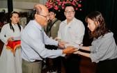 福建勵學會副會長、溫陵會館常值副 理事長洪世真(前左)向優秀生頒發獎學金。